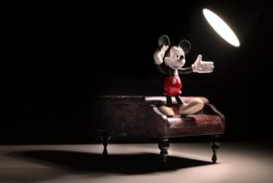 Mickey Mouse figurine standing on a toy piano