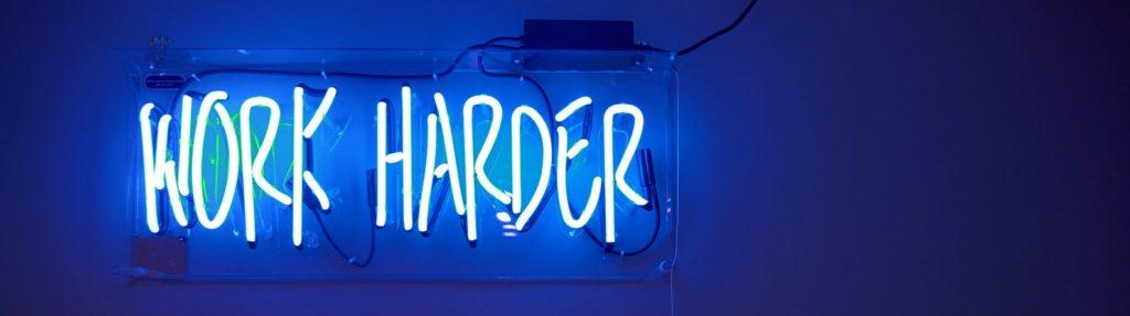 neon sign saying work harder