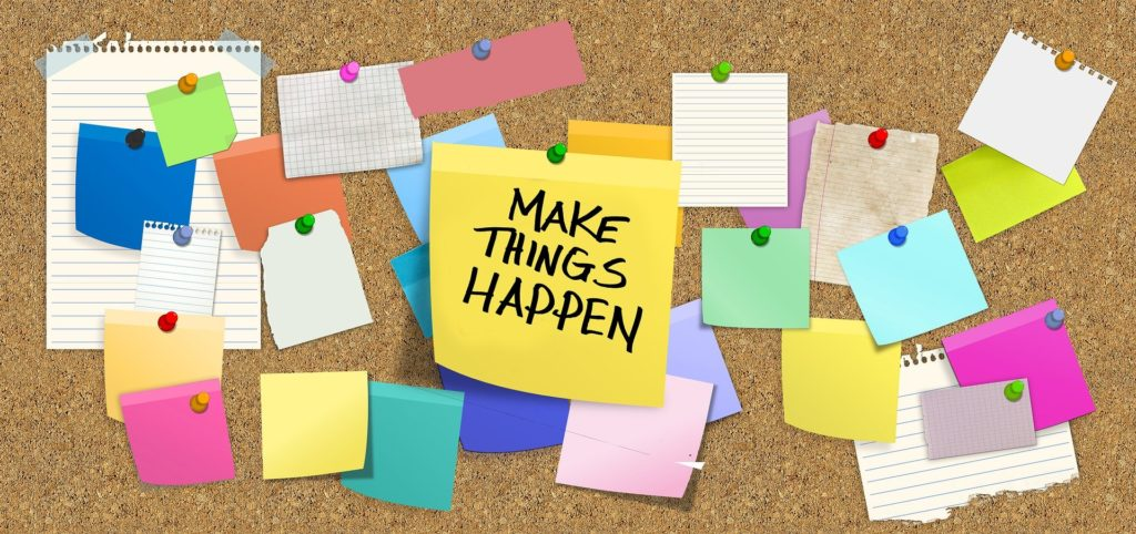 cork bulletin board with post it notes, one saying Make Things Happen