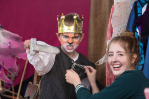 Boy in king costume with a woman helping him