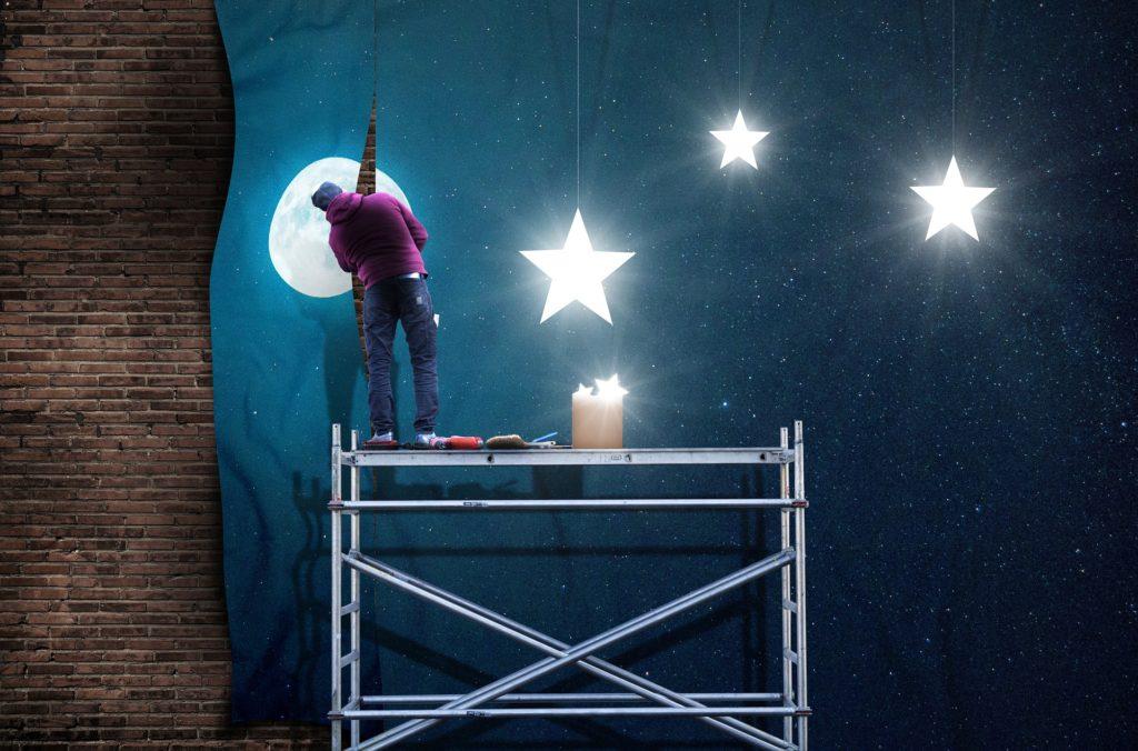 backstage man on scaffold painting stars