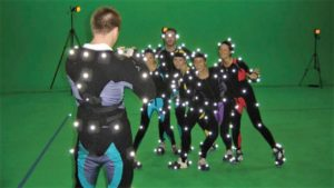 actors in front of a green screen with motion capture suits on