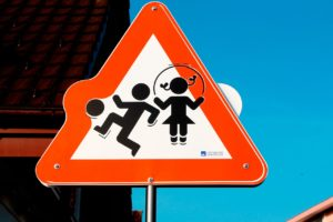 caution sign with kids playing