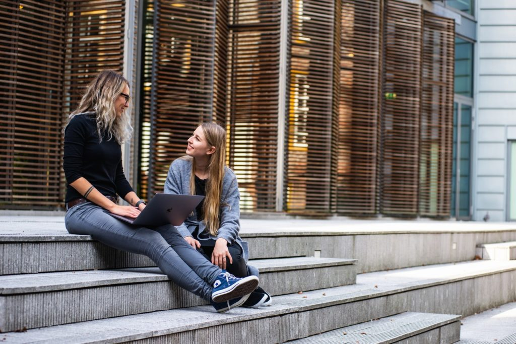 two women sitting on steps