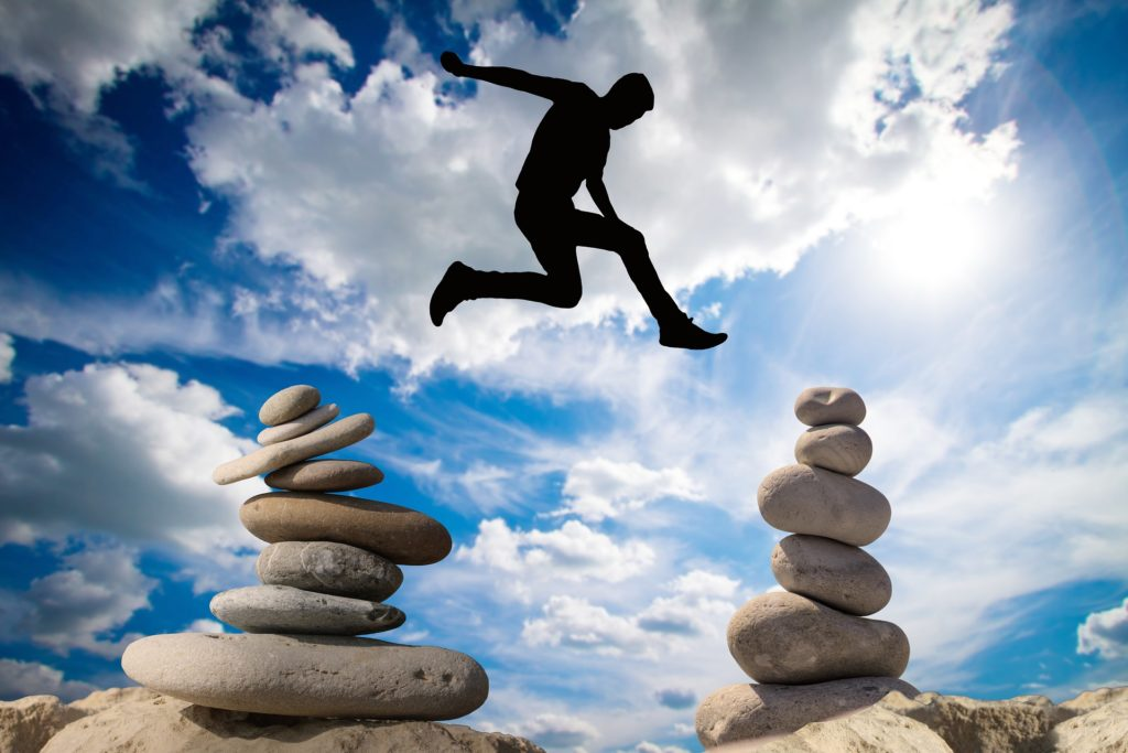 man leaping from rock to rock
