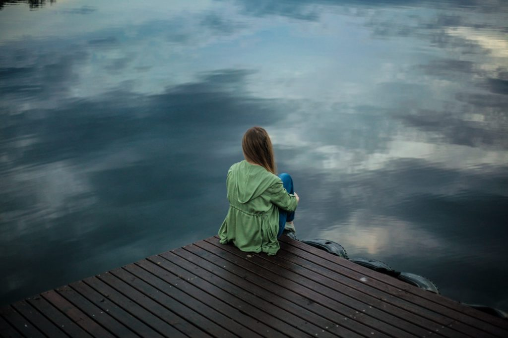 woman sitting on a pier