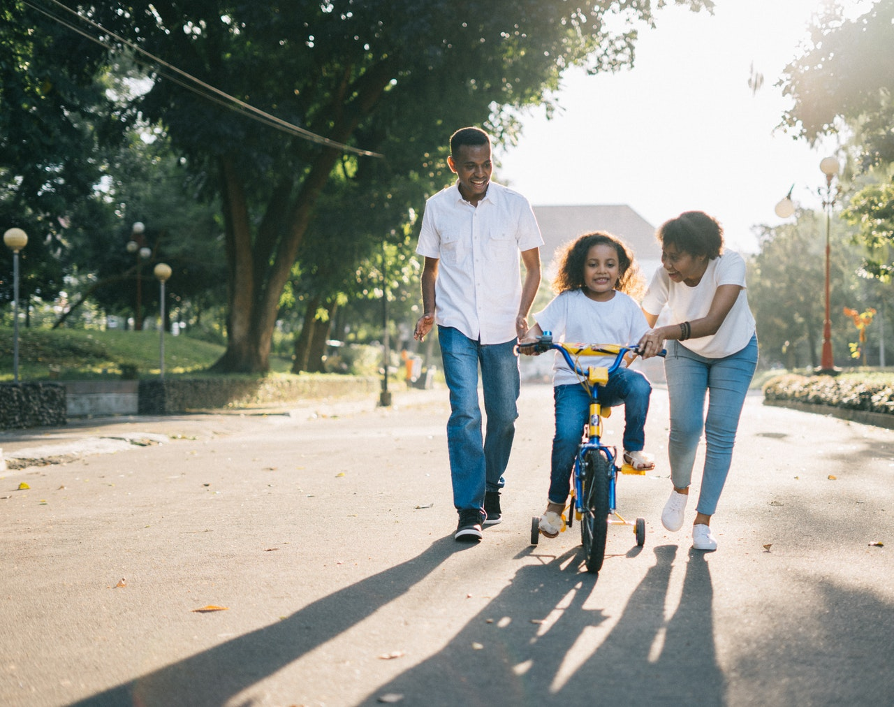 Girl on Bike with man and woman assisting her