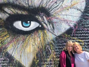Anne and Lisa in front of mural with an eye