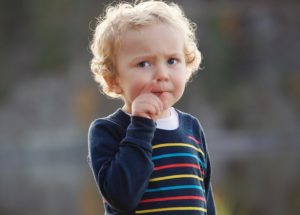 blonde boy looking thoughtful